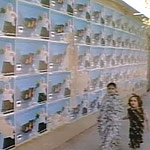 Two girls walk past a wall covered with election posters for one candidate