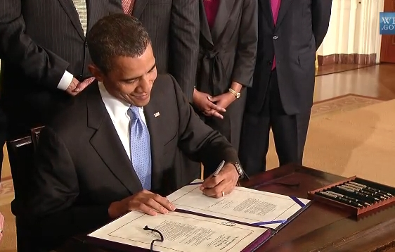 President Obama signing Iran Sanction Act in June 2010