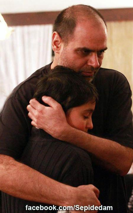 Mojtaba Mirtahmasb hugs his son Yasna after he was released from jail