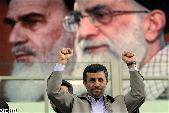 Ahmadinejad with Khomeini and Khamenei portraits in the background