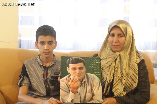 Fatemeh Adinehvand and his son holding Abdollah Momeni's picture