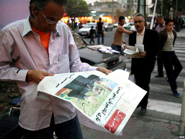 A man reads a newspaper with a story on opposition leader Mir Hossein Musavi on it in Tehran